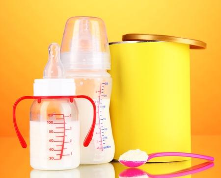 fondo para bebe: Botellas con leche y alimentos para beb�s en el fondo de color naranja