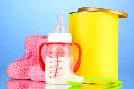 fondo para bebe: Botella con la leche y los alimentos para beb?s en el fondo azul Foto de archivo