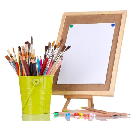 Small easel with sheet of paper with art supplies isolated on white photo