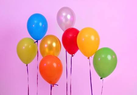 Many bright balloons on pink background photo