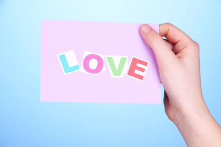 Love word on piece paper in hand on blue background photo