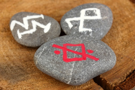 Fortune telling  with symbols on stones on wooden background Stock Photo - 19654933