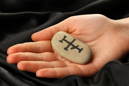 Fortune telling  with symbols on stone in hand on black fabric background Stock Photo - 19654722