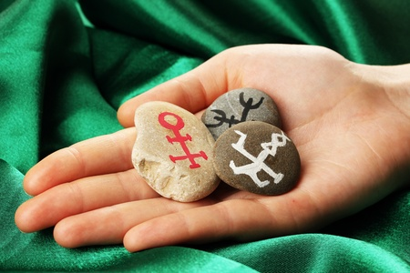 Fortune telling  with symbols on stone in hand on green fabric background Stock Photo - 19654411