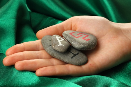 Fortune telling  with symbols on stone in hand on green fabric background Stock Photo - 19655004