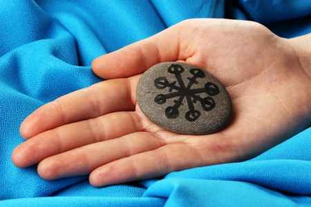 Fortune telling  with symbols on stone in hand on blue fabric background Stock Photo - 19655087