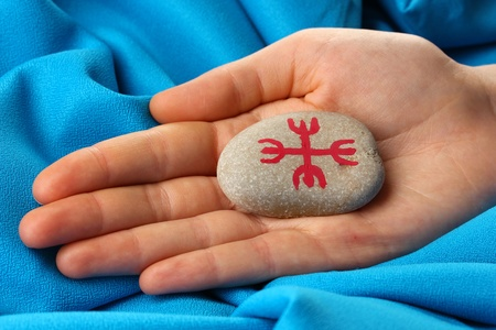 Fortune telling  with symbols on stone in hand on blue fabric background photo