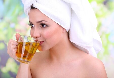 tea towel: Beautiful young woman with cup of herbal tea on bright background Stock Photo