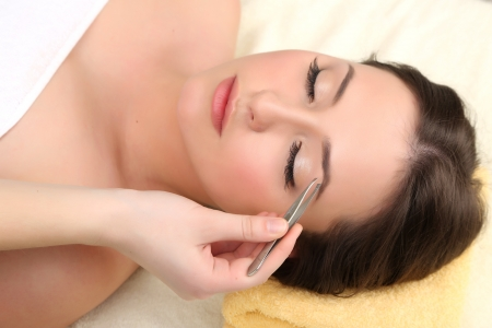 tweezers: Beautiful young woman in cosmetic salon close up