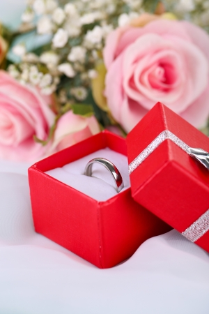 Roses and a ring on a white cloth photo
