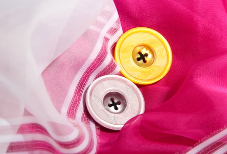 Two buttons on pink and white cloth photo