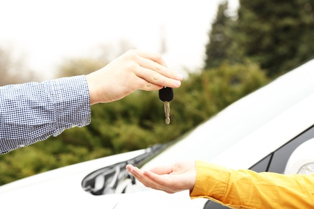 Woman and man hands with car key, close up photo