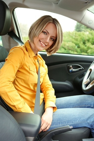 attaching: Portrait of young beautiful woman attaching seat belt in the car Stock Photo