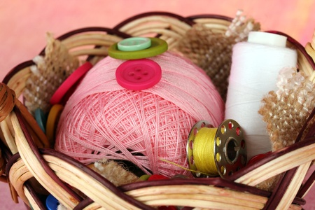 basket embroidery: Variety of buttons and a ball of yarn in a basket on a pink background Stock Photo