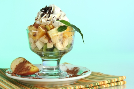 Fruit salad in a sundae dish on a blue background photo