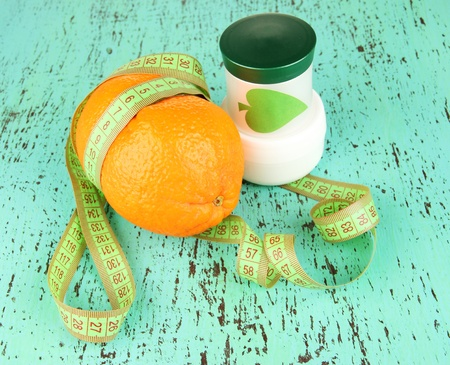 Orange with measuring tape and body cream, on color  wooden background photo