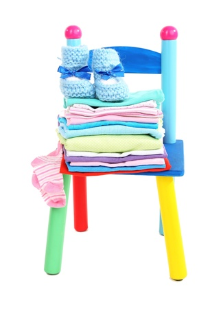 Small and colorful chair with baby clothes isolated on white Stock Photo - 19727129