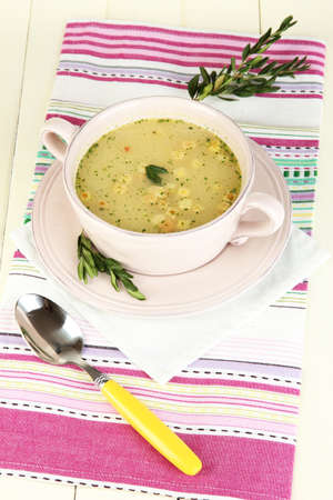 Nourishing soup in pink pan on wooden table close-up photo