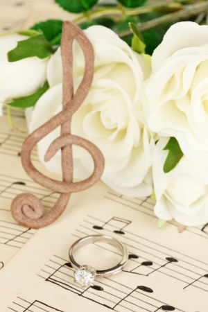 Treble clef, roses and wedding ring on musical background photo