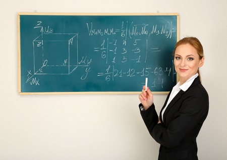 Portrait of teacher woman near the chalkboard in classroom photo