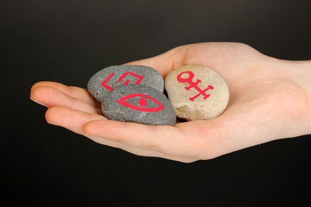 Fortune telling  with symbols on stone in hand on grey background photo