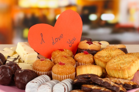 Sweet cookies with valentine card on table in cafe photo
