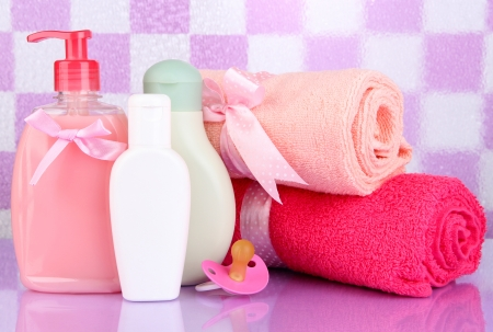 Baby cosmetics and towels  in bathroom on violet tile wall background Stock Photo - 19763362