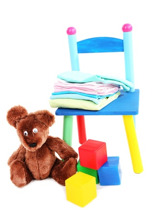 Small and colorful chair with baby clothes isolated on white Stock Photo - 19763295