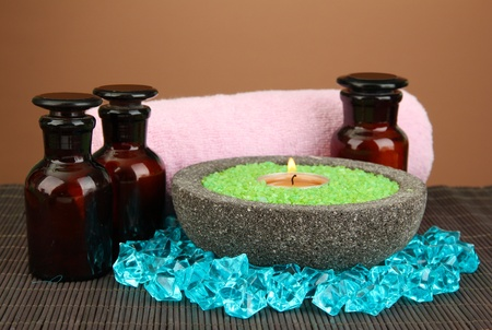 Candle in stone bowl with marine salt, on bamboo mat, on brown background photo