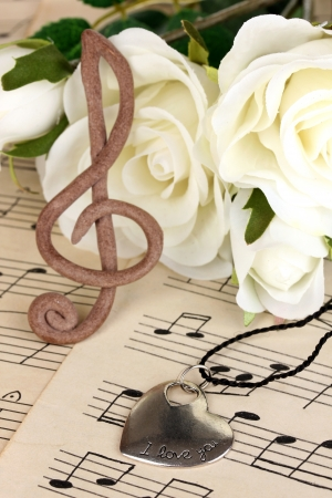 sheetmusic: Treble clef, pendant and roses on musical background Stock Photo