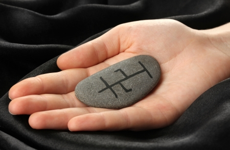 Fortune telling  with symbols on stone in hand on black fabric background photo