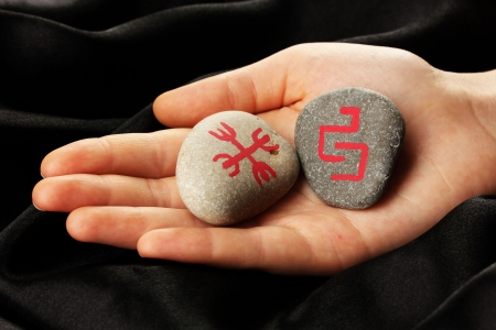 Fortune telling  with symbols on stone in hand on black fabric background Stock Photo - 19763744