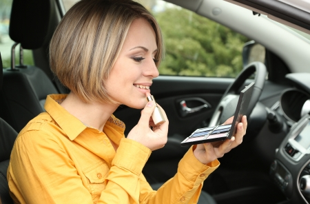 Portrait of young blond woman applying makeup while in the car photo