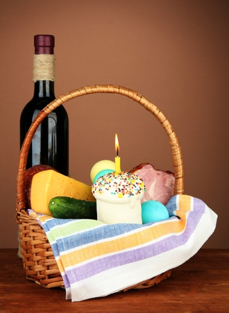 Easter basket: Conceptual photo of traditional easter food in wicker basket, on wooden table on color background photo