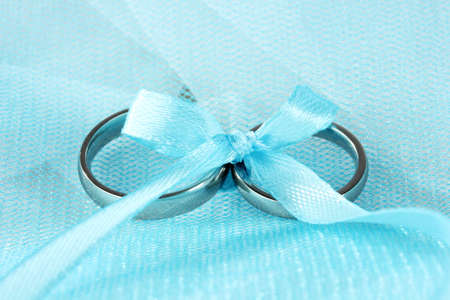 Wedding rings tied with ribbon on cloth background Stock Photo