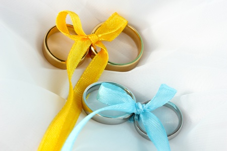Wedding rings tied with ribbon on cloth background photo