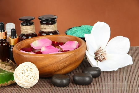 Spa composition with aroma oils on brown background photo