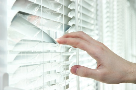 Someone looking out of window opening blinds Stock Photo - 19763570