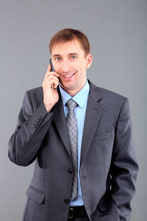 careerists: Young businessman talking over cell phone on grey background