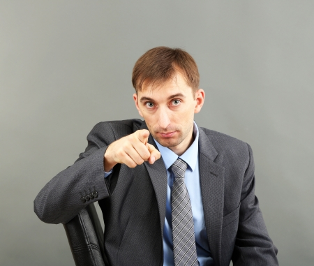 Young businessman  on grey background Stock Photo - 21524297
