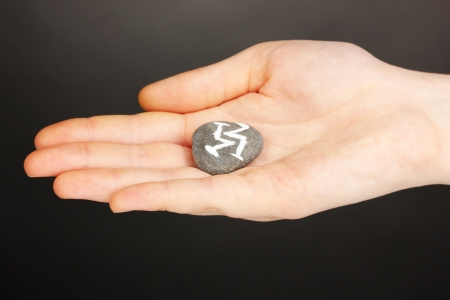 Fortune telling  with symbols on stone in hand on grey background Stock Photo - 19766846