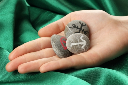 Fortune telling  with symbols on stone in hand on green fabric background Stock Photo - 19767162