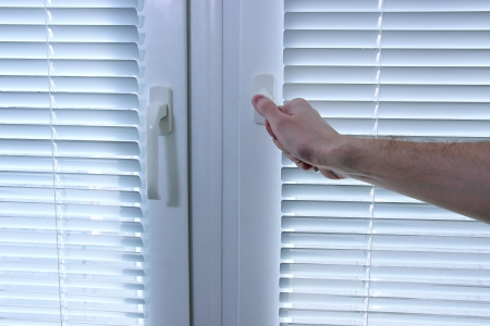 Someone opens metal-plastic window blinds closed Stock Photo - 19767060