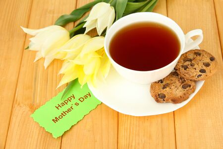 Composition of tulips and cup with some drink, on wooden background photo