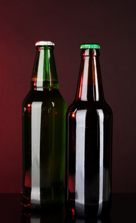 Bottles of beer on brown background photo