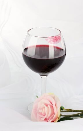 glass of white wine: Glass of wine with lipstick imprint on white fabric background Stock Photo