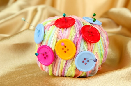 Colorful buttons and multicolor wool ball, on color fabric background photo