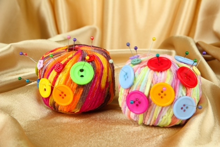 Colorful buttons and multicolor wool balls, on color fabric background photo