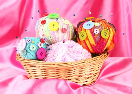 wicker work: Colorful buttons and multicolor wool balls in wicker basket, on color fabric background