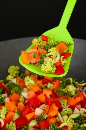 Vegetable ragout in wok, isolated on black photo